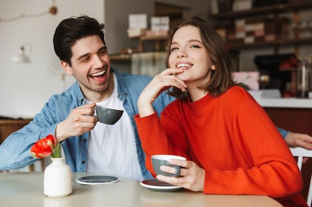 Casal feliz, mulher e homem sorrindo e se divertindo no café, enquanto bebem café ou chá pela manhã