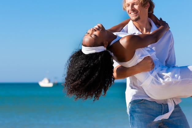 Casal feliz - mulher negra e homem caucasiano - na praia em suas férias