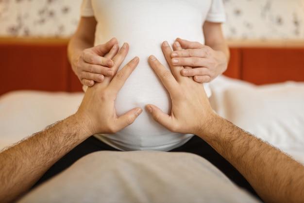 Casal feliz na cama, marido tocando a barriga de sua esposa grávida. gravidez, período pré-natal. mamãe e papai expectantes estão descansando, cuidados de saúde