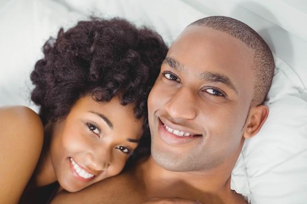 Casal feliz na cama sorrindo para a câmera em casa
