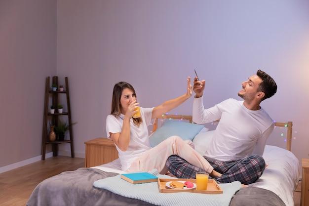 Casal feliz na cama tirando fotos