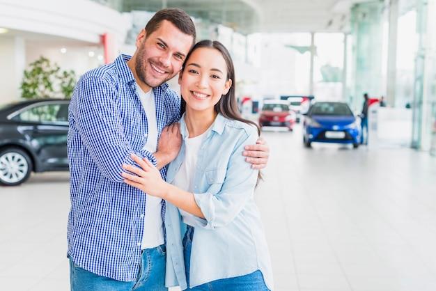Casal feliz na concessionária de carros