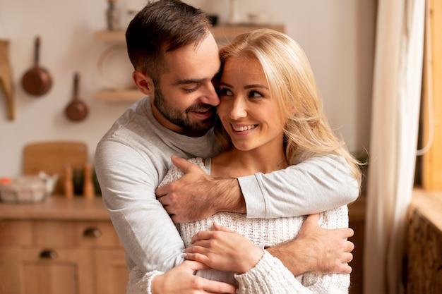 Casal feliz na cozinha com tiro médio