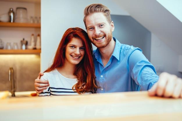 Casal feliz na cozinha sorrindo depois de se mudar para a nova casa
