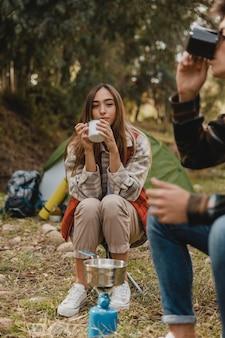 Casal feliz na floresta bebendo chá
