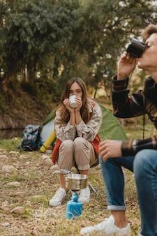 Casal feliz na floresta bebendo em canecas