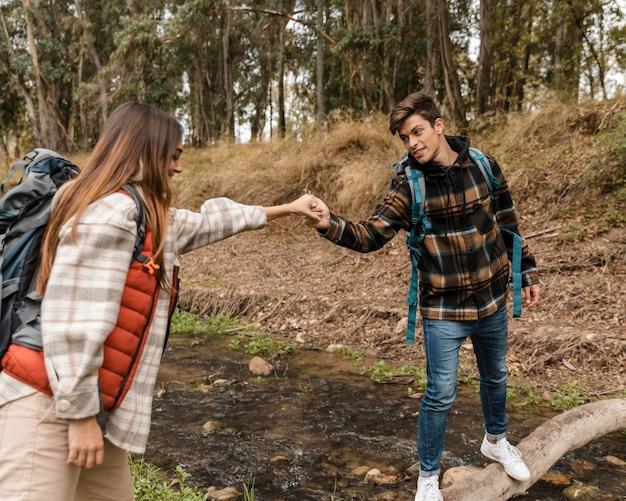 Casal feliz na floresta de mãos dadas