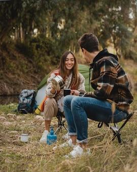 Casal feliz na floresta estando juntos no acampamento