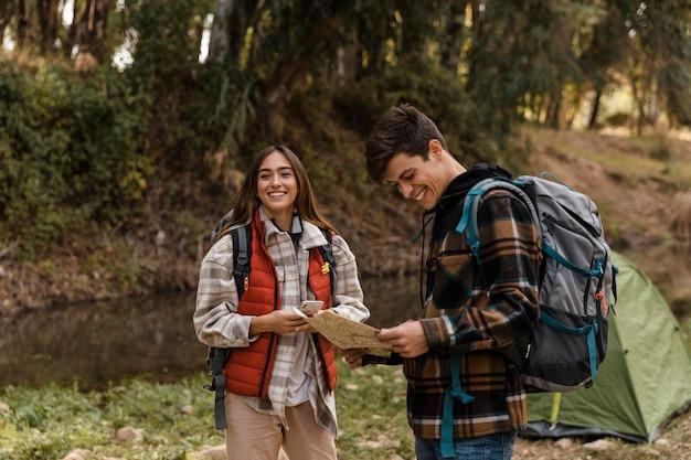 Casal feliz na floresta lendo um mapa