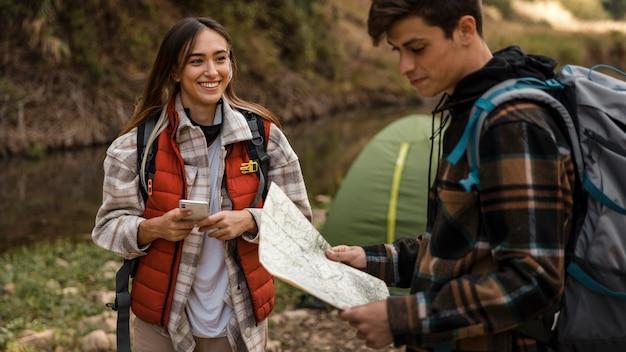 Casal feliz na floresta olhando um mapa