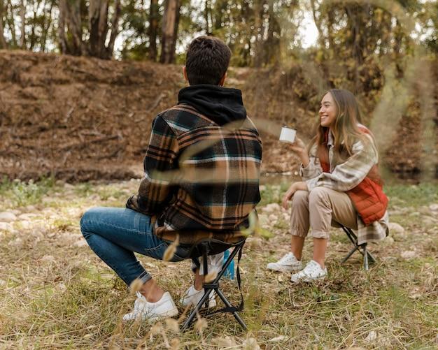 Casal feliz na floresta por trás de tiro