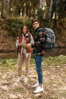 Casal feliz na floresta segurando um mapa.
