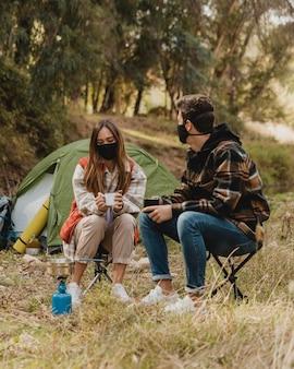 Casal feliz na floresta usando máscaras médicas