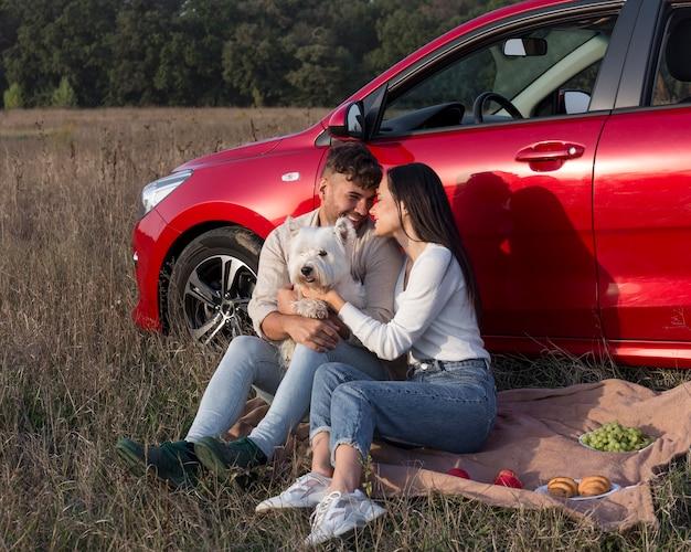 Casal feliz na grama com cachorro
