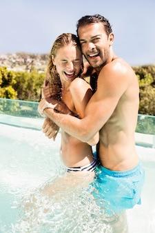 Casal feliz na piscina abraçando e rindo