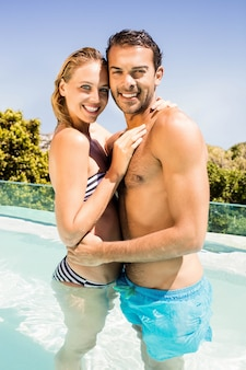 Casal feliz na piscina abraçando