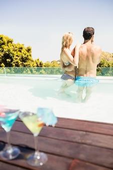 Casal feliz na piscina com cocktails à beira