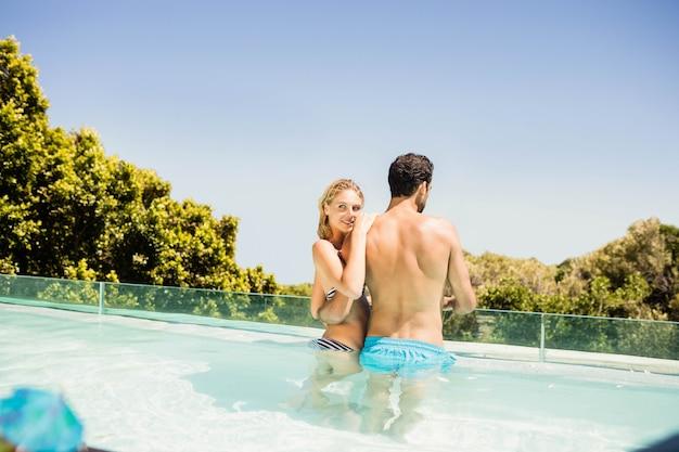 Casal feliz na piscina em um dia ensolarado