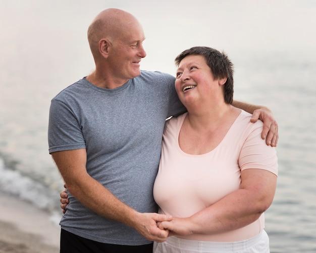 Casal feliz na praia tiro médio