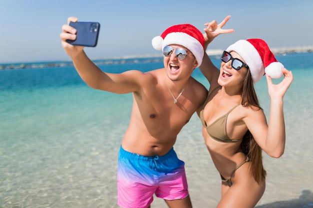Casal feliz nas férias de viagem de natal tirando foto de selfie com smartphone usando chapéu de papai noel