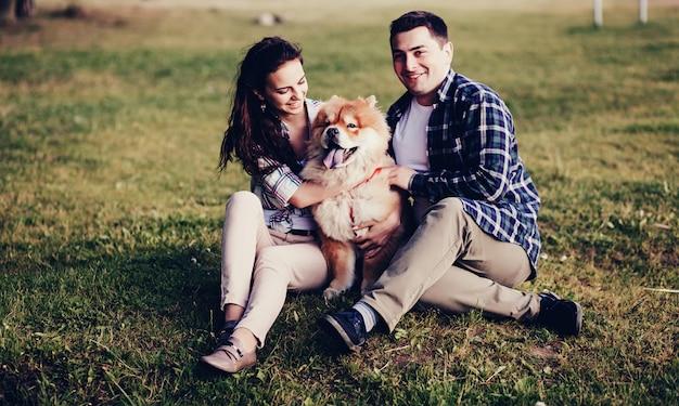 Casal feliz no amor abraçando um cachorro