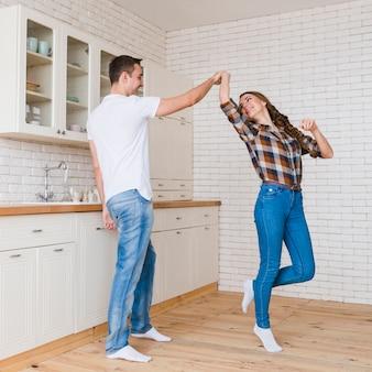 Casal feliz no amor dançando na cozinha