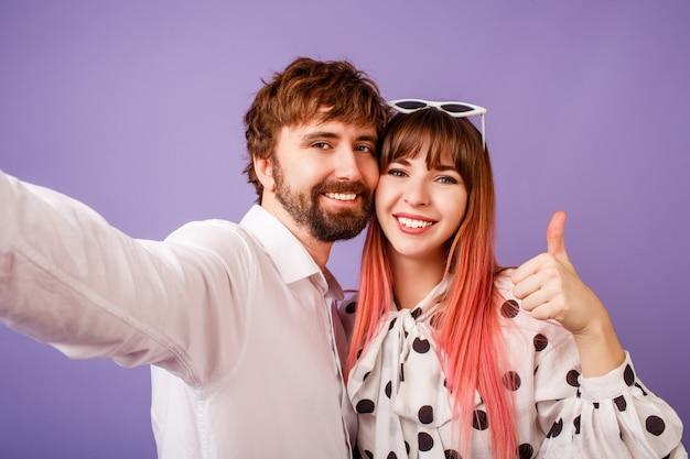 Casal feliz no amor fazendo auto-retrato na parede roxa