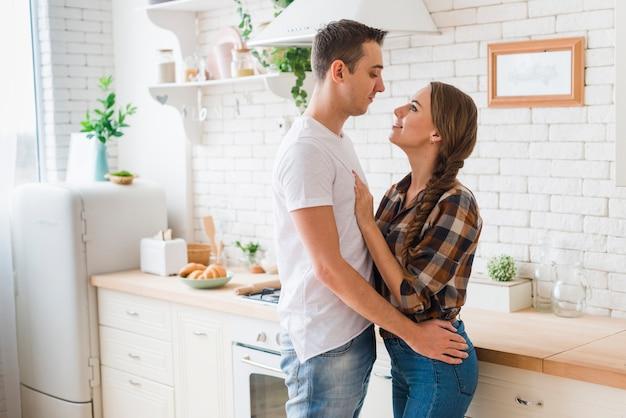 Casal feliz no amor juntos abraçando na cozinha