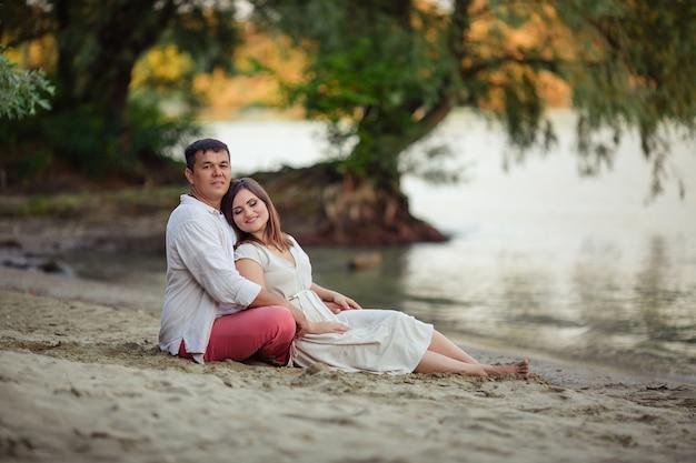 Casal feliz no amor marido e mulher estão sentados em uma caminhada na areia à beira do rio no verão de férias.