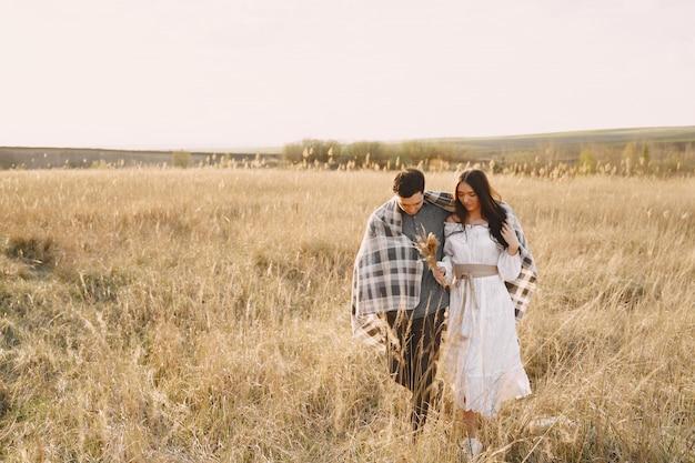Casal feliz no amor no campo de trigo ao pôr do sol