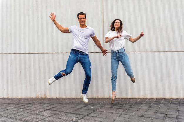 Casal feliz no amor pulando contra parede cinza.