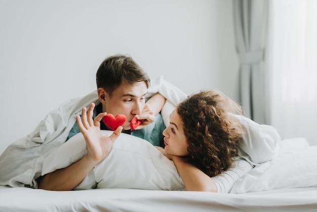 Casal feliz no amor sob o cobertor