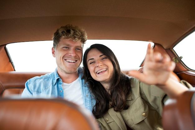 Casal feliz no carro com tiro médio