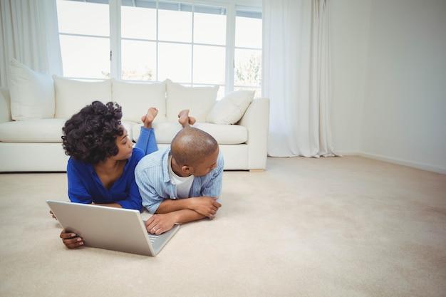 Casal feliz no chão com laptop