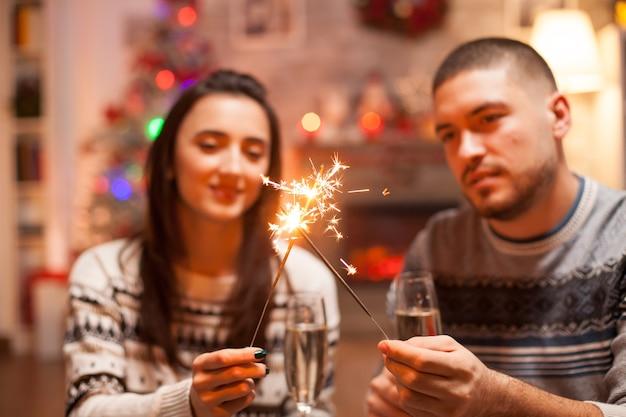 Casal feliz no dia de natal, segurando fogos de artifício de mão.