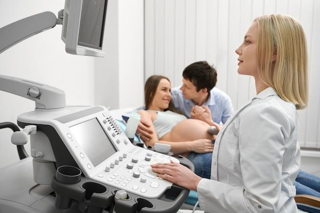 Casal feliz no exame de ultrassom da mulher grávida.