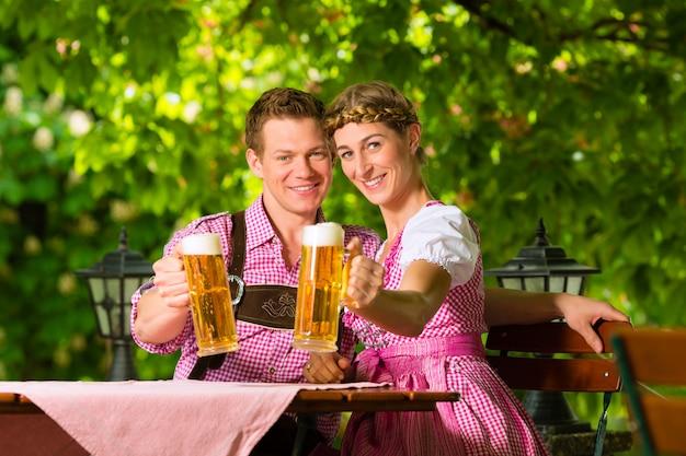 Casal feliz no jardim da cerveja bebendo cerveja