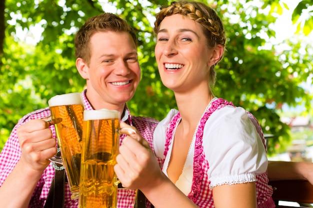 Casal feliz no jardim de cerveja bebendo cerveja