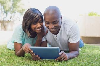 Casal feliz no jardim usando tablet pc juntos