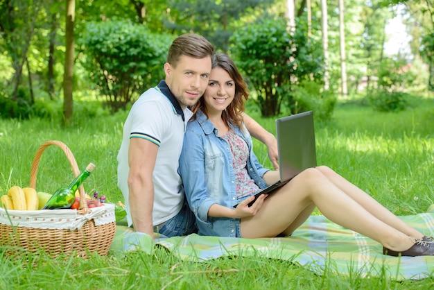 Casal feliz no piquenique com o laptop no parque.