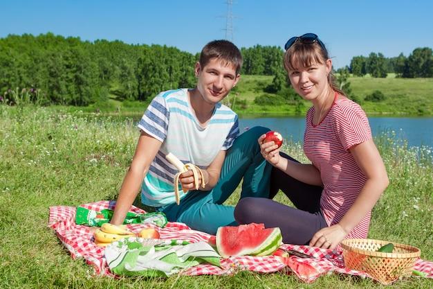 Casal feliz no piquenique no lago comendo frutas, se divertindo juntos. retrato ao ar livre