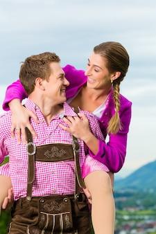 Casal feliz no prado alpino em tracht