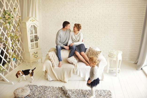 Casal feliz no sofá-cama da sala.