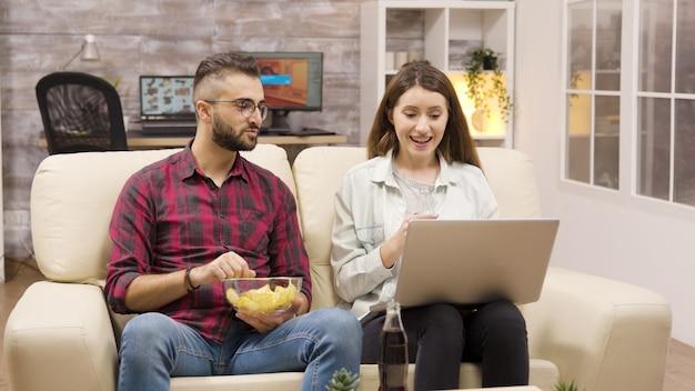 Casal feliz no sofá comendo batatinhas e olhando para um laptop