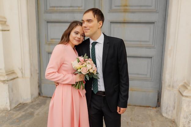 Casal feliz noivos perto da porta da igreja.