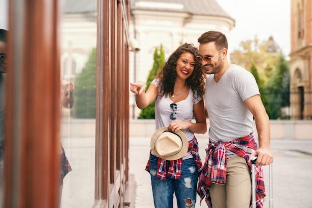 Casal feliz olhando a vitrine. mulher apontando para a janela enquanto homem segurando a bagagem. conceito de viagem.