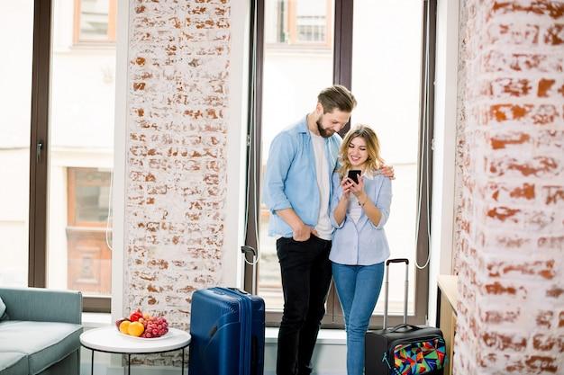Casal feliz olhando as fotos em um telefone inteligente em cima da janela