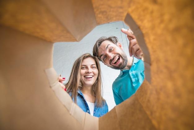 Casal feliz olhando dentro do saco de papel