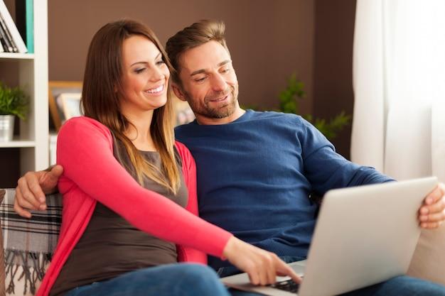 Casal feliz olhando para a tela do laptop no sofá em casa