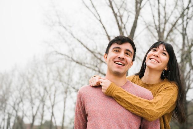 Casal feliz olhando para longe com alegria no parque